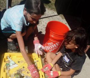 Colleen Munroe and her grandson, Kaiden Castillo, sort through debris found in the mangroves. (Source photo by Susan Ellis)