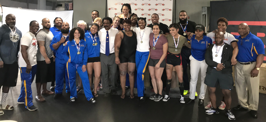 The powerlifting competitors pose for a group picture after the event. (Source photo by Kyle Murphy)