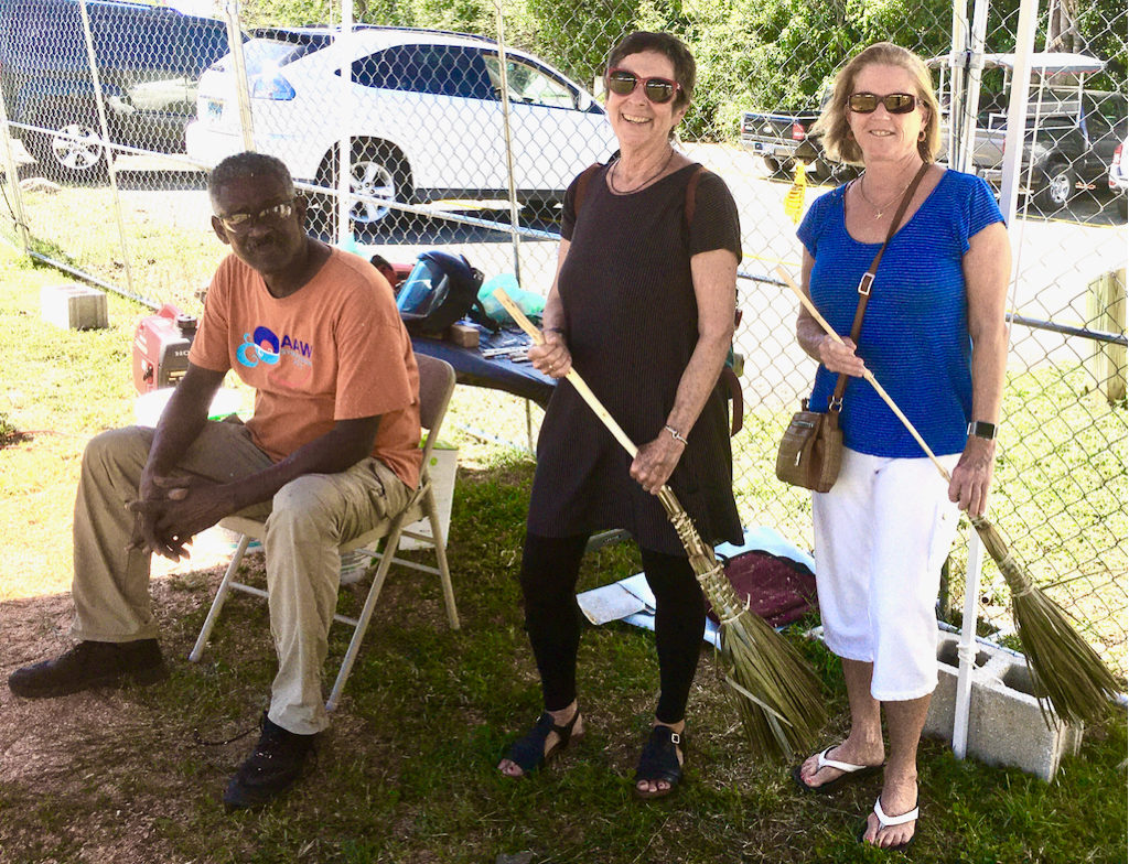 Avelino Samuel looks on while Barbie Devine and Sherri Draper wield their new brooms, woven by Edmund Roberts. (Source photo by Amy Roberts)