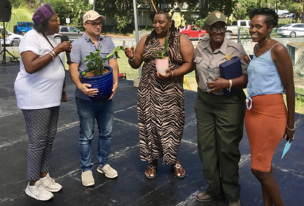 Golda Hermon, second from right in NPS uniform, is recognized for her work organizing the 29th Folklife Festival by St. John Community Foundation members, from left, Alecia Wells, Jon Eichner and Abigail Hendricks, and Dior Parsons, right. (Source photo by Amy Roberts)