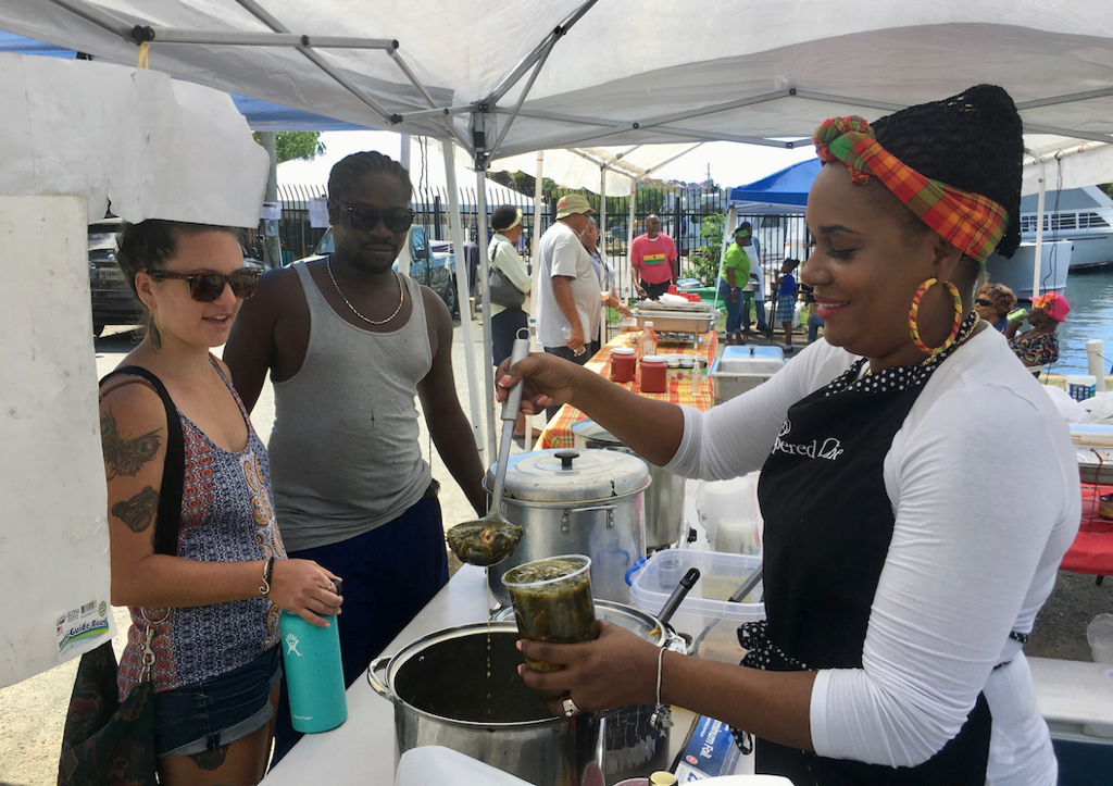 Luciah Polius serves up kallaloo to Darby Rutledge and Adiso Henry. (Source photo by Amy Roberts)