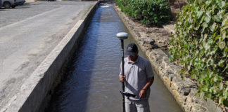 Greg Guannel, director of UVI's Caribbean Green Technology Center, measures sediment depth in the gut that empties near the seaplane terminal in Christiansted. (Photo submitted by Hilary Lohmann, DPNR)