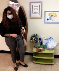 """Cabrera stands by her """"No Mask, No Service """"sign and sanitizing station."""