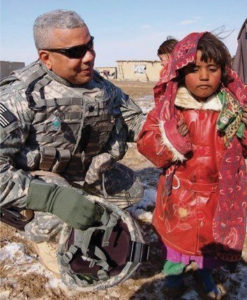 Lt. Col. David C. Canegata III, who served in the Persian Gulf War in Afghanistan, spends a moment with a local girl (Photo provided by Nicole Canegata)