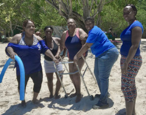 Staff from Queen Louise Home for the Aged help a resident use her walker in the sand in this 2015 photo. (Photo provided by V.I. Human Services)