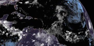 A satellite photo taken at 12:20 a.m. shows a disorganized tropical wave east of the Caribbean, and another system off the coast of North Carolina and heading out into the Atlantic. (NOAA photo)