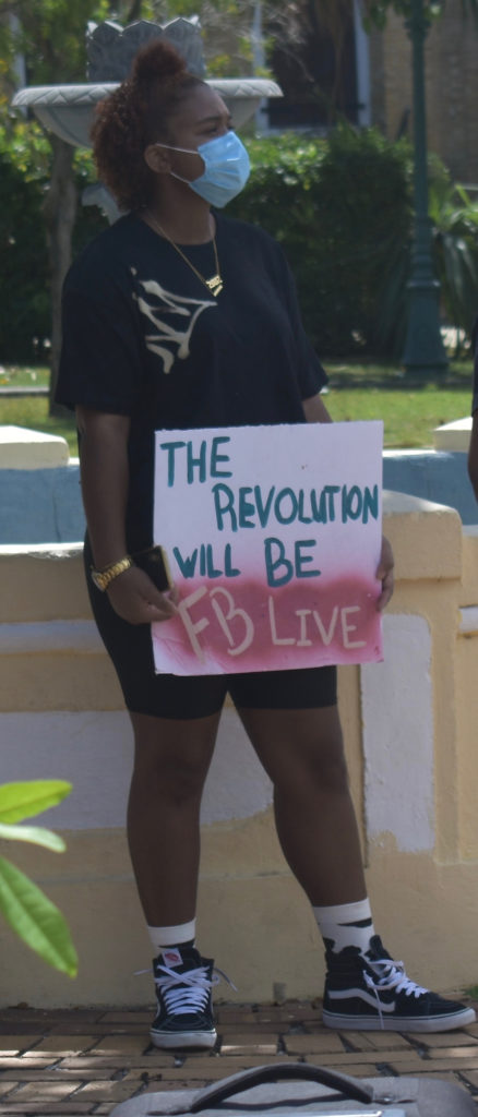 """A sign reads """"The revolution will be FB Live"""" a reference to the amount of viral videos about the protest worldwide and a play on the 1960s Black Panther slogan, """"The Revolution Will Not Be Televised."""" (Source photo by Kyle Murphy)"""