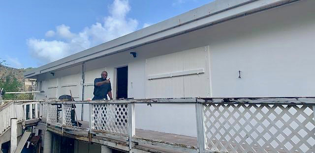 The Rev. Anthony Abraham gives the thumbs up as the congregation begins repairs on Charity House near Cruz Bay. photo provided by OLMC Catholic Church. (Source photo by Amy H. Roberts)
