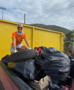 Jody Olsen, who helped organize the clean up, sits on top of debris picked up over the two days. (Photo provided by Jody Olsen)