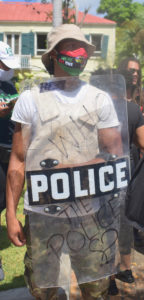 """A protesterin police riot gear asks """"Who Police the Police? (Source photo by Kyle Murphy)"""