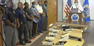 At a news conference Tuesday, St. Croix Police Chief Sidney Elskoe, at the podium, announced four arrests and the seizure of 10 illegal firearms, which were on display. (Source photo by James Gardner)