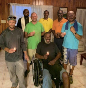 The Rev. Anthony Abraham blesses the Our Lady of Charity House in March. Standing, from left, are resident Jerry Newton, the Rev. Anthony Abraham, resident Josh Libby, deacons Cassius Mathurin and Evans Doway and resident Kevin Benton Jr. gather around Ervince 'Hollywood' Phillip.