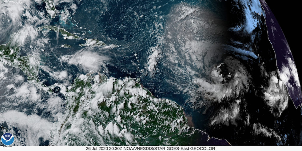Satellite photo shows the remnant of Gonzalo blowing off to the left, while Invest 92-L comes across from the right, heading for the Caribbean. (NOAA satellite photo)