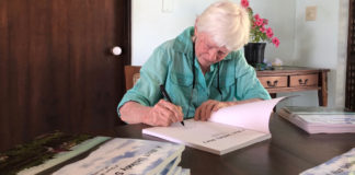 """Author and painter Emy Thomas signs copies of her new book. """"A Most Unlikely Story."""" (Source photo by Susan Ellis)"""