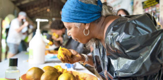With her left hand behind her back, this mango-eating contestant dives into the plate of tropical fruit. (Photo provided by DEAR Productions Photography)